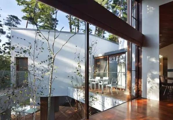 几间房屋用走廊进行连接,  走廊两侧是通透的落地玻璃,  一年四季的图片